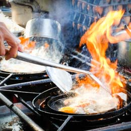Johnson Gas - Gas plumber Adelaide, image of commercial gas stove, chef cooking flaming seafood dish.